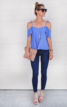 Chica usando una blusa sin hombros de color azul y pantalón de mezclilla, sosteniendo una bolsa tipo clutch de color café