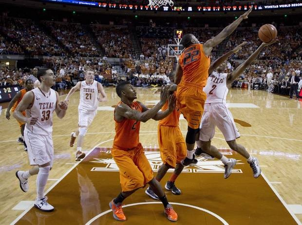 Texas' Demarcus Holland (2) shoots as Oklahoma State's Markel Brown (22), Le'Bryan Nash (2) and Kamari Murphy, center, defend