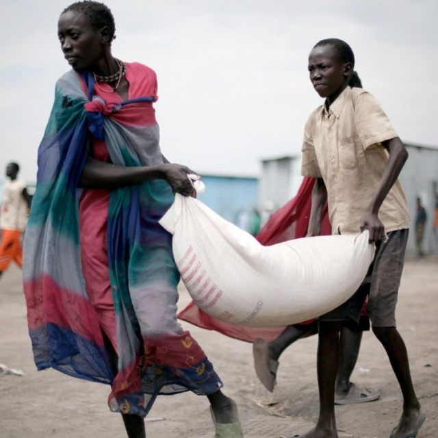 South Sudanese women carry food aid from a World Food Program distribution center in Pibor, South Sudan, Jan. 12.