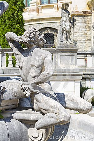 Allegoric stone male statue of a fountain in Peles castle garden, Sinaia, Romania. Peles castle is the most visited museum in Romania with more than 300.000 tourists every year.