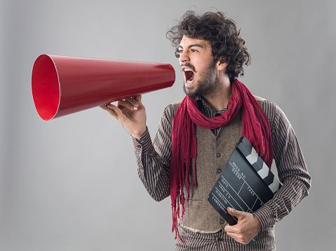 Young film director shouting through megaphone