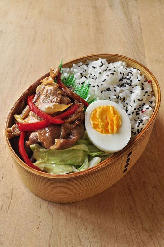 """Grilled Beef """"Yakiniku"""" bento box, with grilled red peppers, hard boiled egg, cabbage salad, and black sesame rice."""