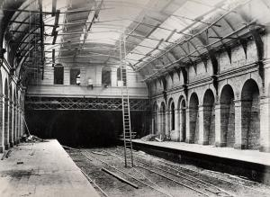 Edgware Road station, Metropolitan Railway, looking west, during construction. It can be seen that the walls, platforms and roof are substantially complete, although scaffolding is still in place below the latter. A man is working on the building between the platforms (background centre) perched somewhat precariously on a plank suspended between two of the windows. Piles of rubble are visible on both platforms. The tracks appear to be of a temporary nature.    Unknown photographer, circa…