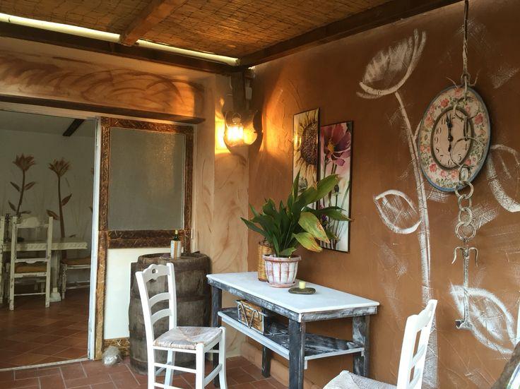 Arredamento creato con mobili restaurati e pareti dipinte in modo particolare a mano libera.