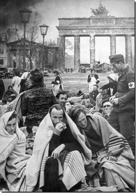 German POW, broken men, and civilians get medical attention in the open near Brandenberg gate. April 1945, Berlin.