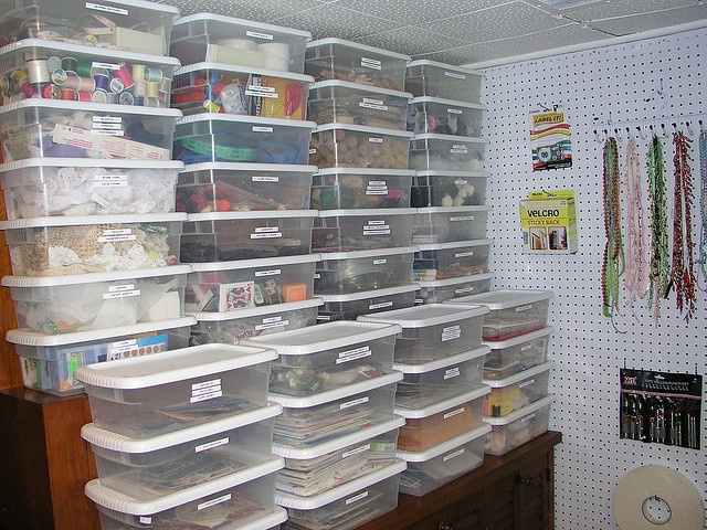 Craft supply storage using plastic shoe boxes.