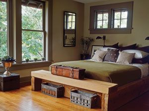 """Brown and Olive colored decor & bed, masculine bedroom: """"For the master bedroom, a chunky cedar bed offers rough-around-the-edges appeal to a darker palette of olives greens and deep brown. For a masculine touch, an antique leather surveyor's case rests at the edge of the bed frame. Old zinc Popsicle molds reside neatly beneath a footboard-bench and may pressed into service as vases."""""""
