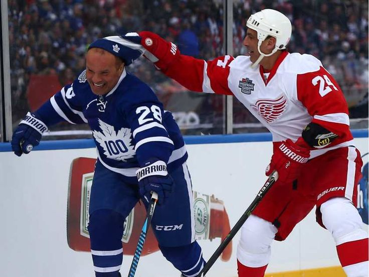 Tie Domi of the Toronto Maple Leafs gets his hat stolen by Chris Chelios of the Detroit Red Wings at Exhibition Stadium during the Centennial Classic Alumni Game in Toronto on Saturday December 31, 2016.