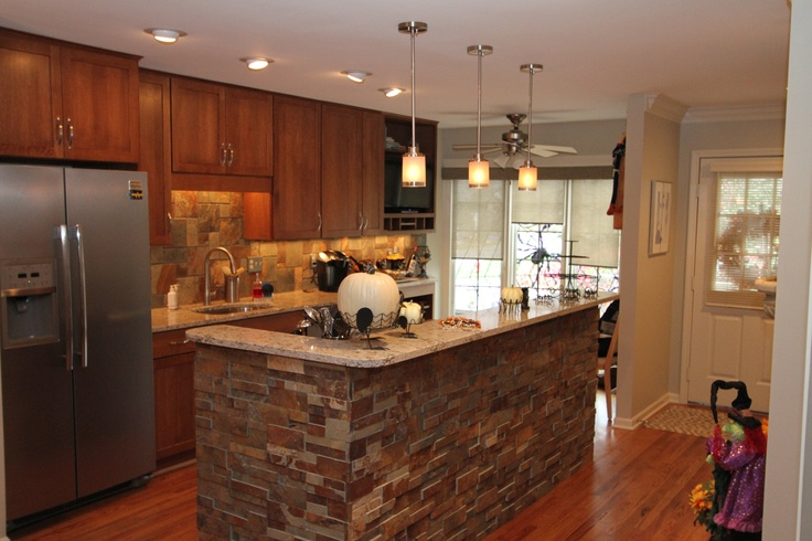 open kitchen with cultured backsplash accent wall