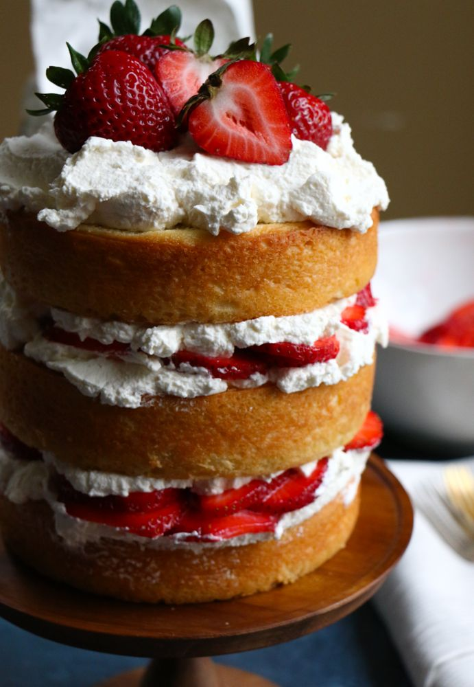 Strawberry Layer Cake with fresh homemade whipped cream and strawberries! Fresh, light and delicious! This is sure to be a show stopper at any party or special gathering!