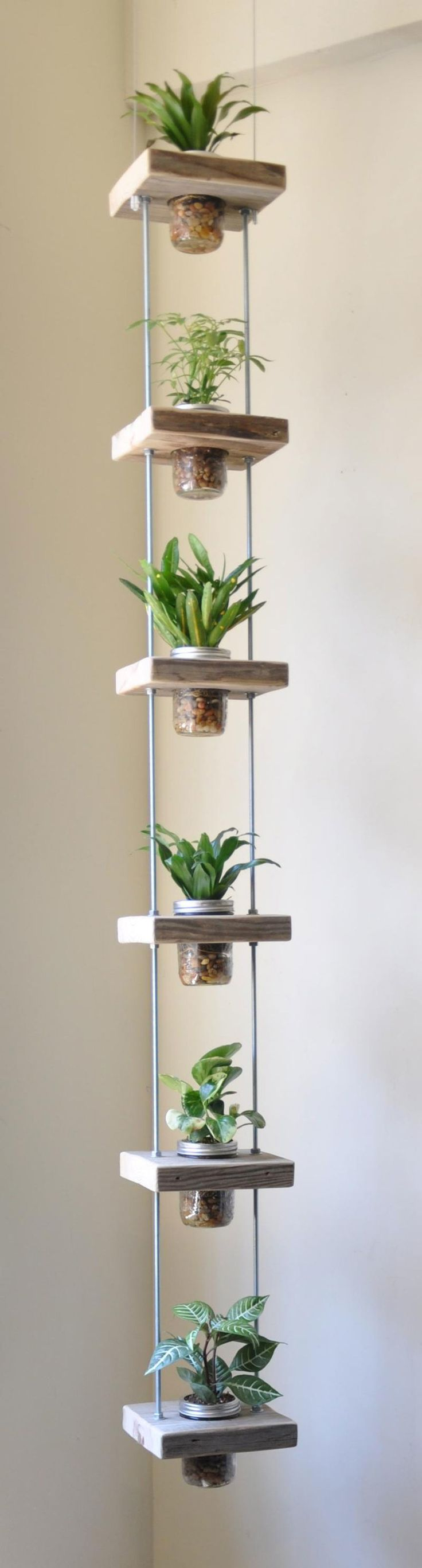 Here, Mason jars are suspended from wooden squares attached to two hanging metal cables. Pro tip: Make sure to line the bottom of your Mason jars with small rocks or pebbles—since there are no drainage holes, this will allow the roots more room to breathe. Get the tutorial at Constant Contact.