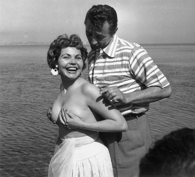 1954: Simone Silva poses topless with Robert Mitchum during the Cannes film festival. Having been elected 'Miss Festival', Simone Silva was asked to leave the festival after her semi-nude pose which resulted in one photographer breaking his arm and another his leg in the rush for pictures