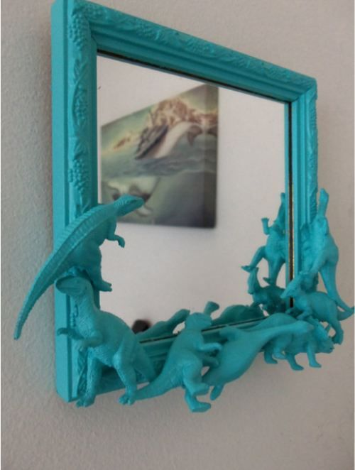 Rawr! How awesome! Glue cheap dinosaurs to a frame and spray paint away!