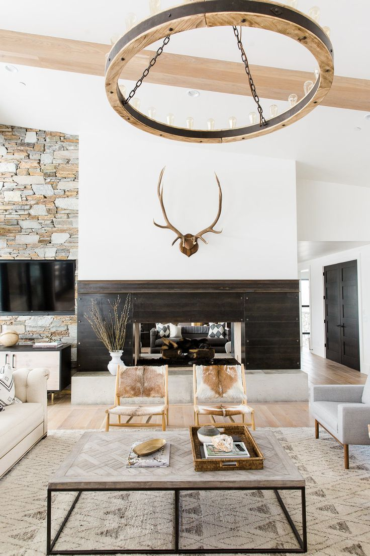 Stunning, rustic-modern living room with light hardwood floors, a farmhouse chandelier, and exposed wooden beams | Studio McGee