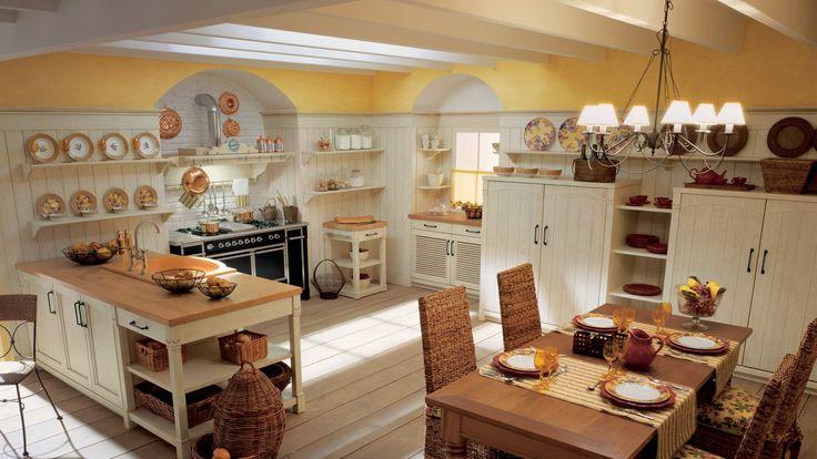 Cucina in legno con penisola, finitura Bianco Burro Anticato. Tavolo Torciglione in finitura Ciliegio, sedie Fiji in foglia di banano intrecciato.