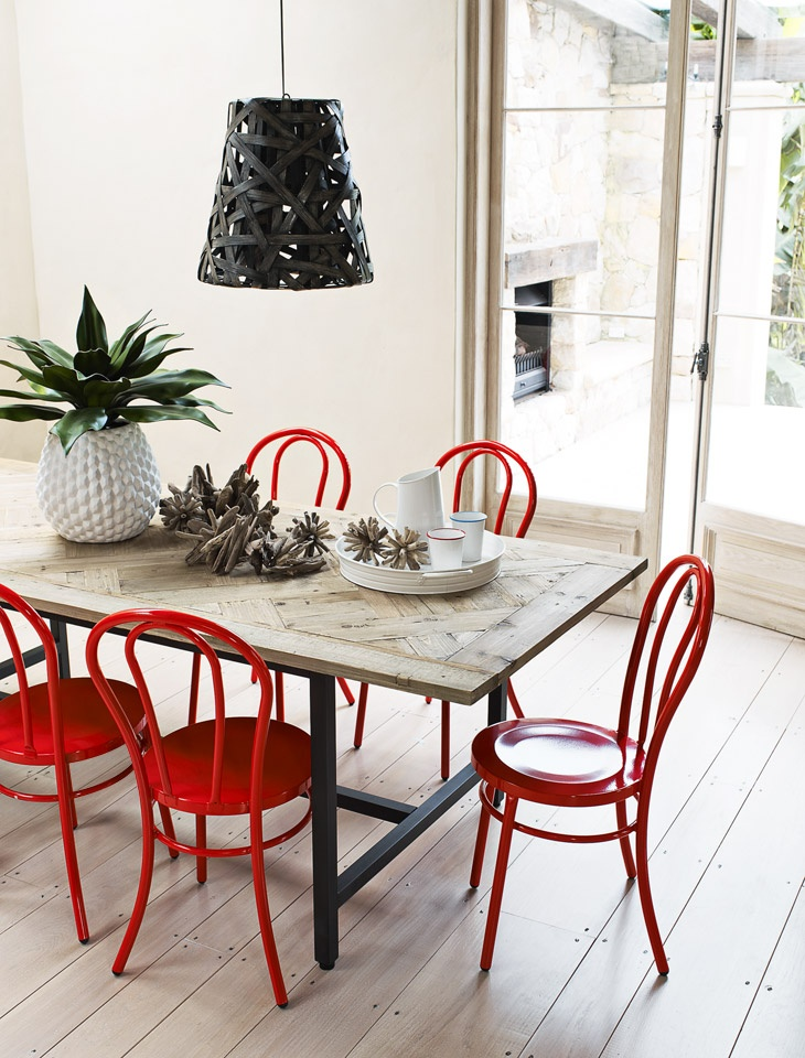 Mixing red bentwood chairs with an industrial / rustic table looks great here. And the wooden table still looks great against floorboards, too