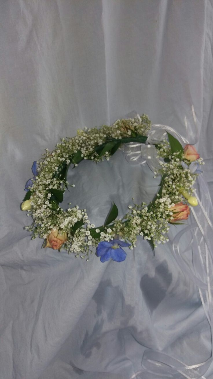 A fall wedding. Featuring pink roses and baby's breath. Accented with calla lilies, blue hydrangea, blue delphinium, and stephanotis. This is a wreath / floral crown done for the jr. Bridesmaid/ flower girl.