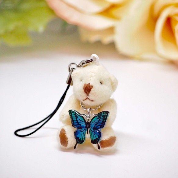 「青い蝶」それは神様の化身。ネイティブアメリカンの間では、神様の使い。 秘密の願い事を蝶に囁くと、神様に伝えてくれるそうです。また、オーストラリアでは幸運のシンボル「青い蝶」ユリシスが居るそうです。 ユリシスの羽の持つ鮮やかな青色は、宝石のようにキラキラとした輝きを放ち、まさに伝説の蝶を髣髴とさせる美しさです。ユリシスの伝説 ○見ると幸せになれる ○1日に3回見ると「お金持ち」になれる ○肩など体にとまると、より大きな幸福が訪れる ○長寿、富を意味する ○ステップアップの予兆そんな幸せ運ぶ「青い蝶」を皆様の元へ届けるため、プラバン、水彩色鉛筆、レジンを使用し、手のひらサイズのかわいいチビクマのストラップと合わせました。ストラップは取り外しが可能で携帯電話やカバン等に付けでいただけます。お好みのチャームをプラスしたり、チビクマに洋服を着せたりしてアレンジすることが出来ます。蝶素材:プラバン、レジンチビクマサイズ:約4.5〜5㎝×2.5〜3㎝