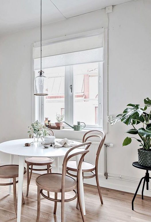 Cozy Dining Room With A White Round Table, Wooden Chairs And A Green Plant.