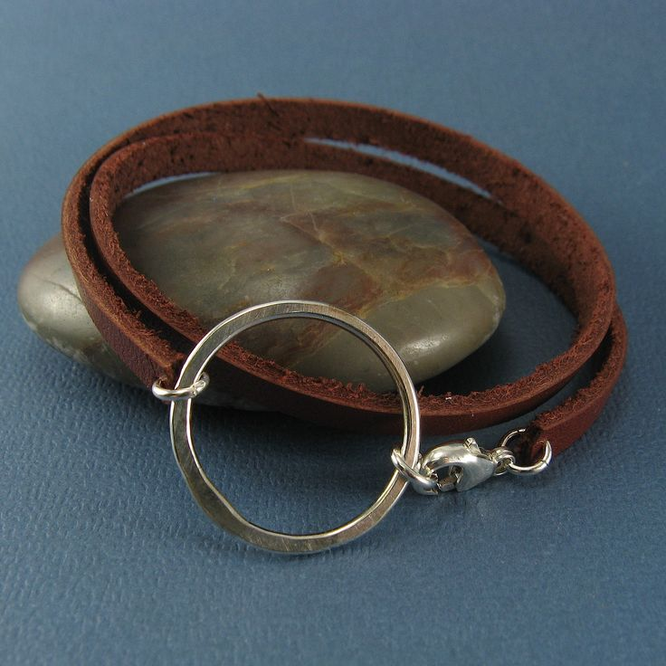 A chunky leather double wrap bracelet with a handcrafted circle centerpiece is ruggedly dainty. The leather is 5mm wide and 2mm thick and the sterling silver centerpiece measures about 1-1/4 inches (3