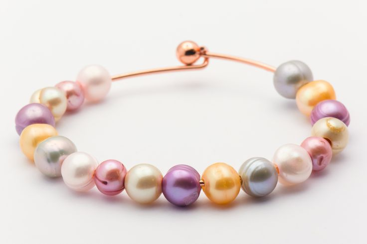 Sweet spring pearl bangle bracelet features abundant color and alluring freshwater cultured pearls. Bangle bracelet is copper plated.
