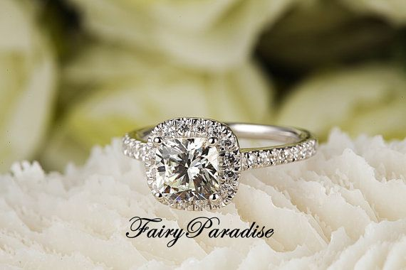 She will love this beautiful and traditional cushion cut halo set engagement ring, with a 2 ct cushion cut center man made diamond and round side