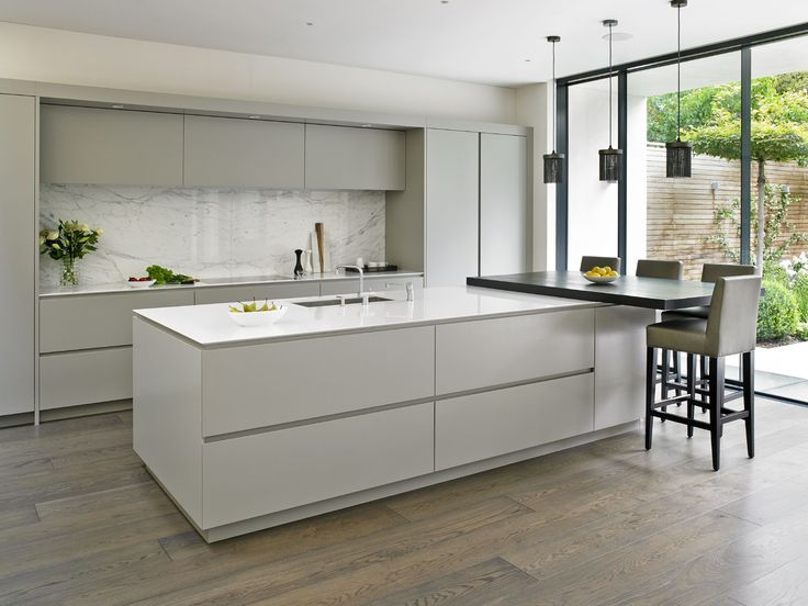 Sleek handleless kitchen design with large island & breakfast bar, marble splashback and floor to ceiling sliding doors leading out into the garden.