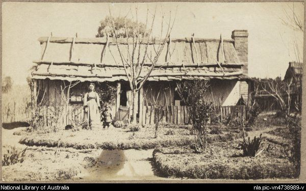 Woman and young boy in formal garden of a slab and rendered cottage with bark roof and paling fence, Hill End, New South Wales, ca.1872 [pi...