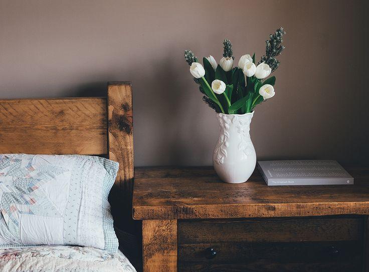 Seng og nattbord i mørkt tre. Hvitt sengetøy og en hvit vase med hvite tulipaner i.