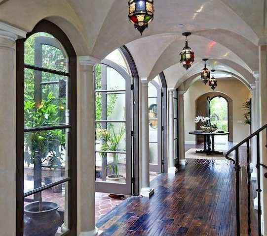 French doors, dark floors, Moroccan lamps, airy hallway, wrought iron bannister, arched ceilings, patio
