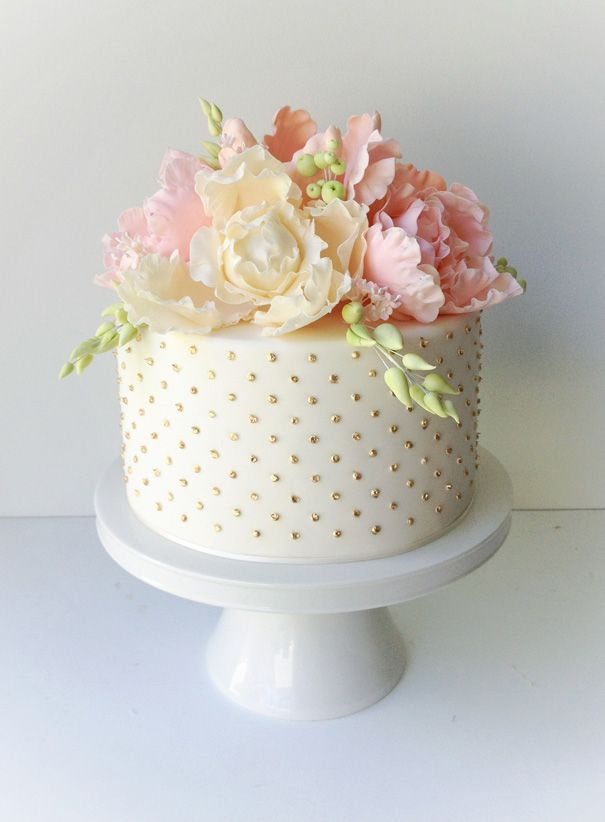 I love the interplay between the floral arrangement and the teensy dots lining the side.  It makes for a very striking little cake.