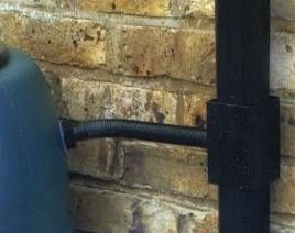 A rainwater diverter fitted to a downpipe directing collected rain into a water butt