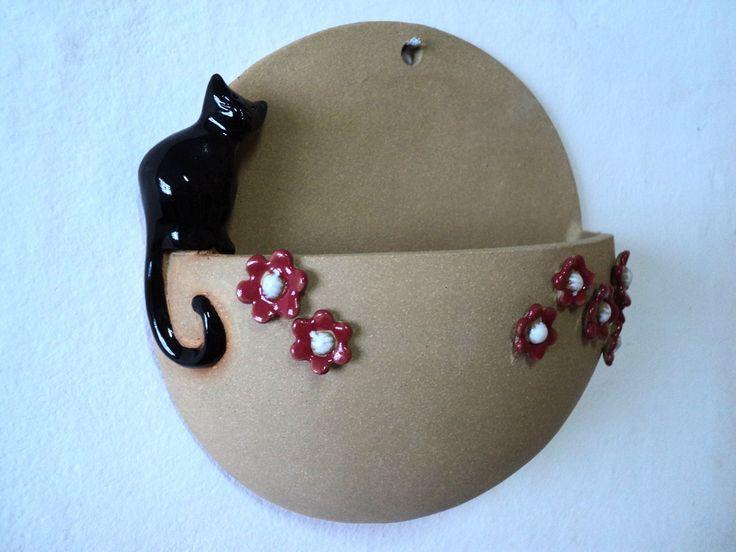 Vaso de parede com flores e gatinho. <br>Feito em cerâmica de alta temperatura, modelado à mão. <br>Pode ter furo para plantar ou sem furo para ser usado como cachepot. <br>O gatinho pode ser feito em outras cores.