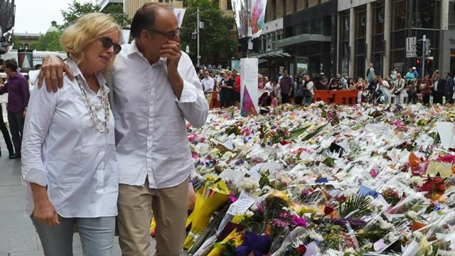 Grieving relatives of Tori Johnson and Katrina Dawson visit the floral tribute to the two Sydney siege victims in Martin Place. (AAP)