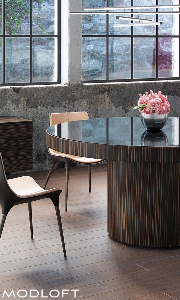 The Berkeley dining table by Modloft represents clean, incisive design. Brilliant painted glass adorns the surface creating a formal contemporary table. Available in exotic cathedral ebony with black glass top or all white lacquer with white glass top. Top diameter measures 63-inch. Seats 6-7 guests.