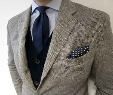 ライトグレーのツイードジャケットに黒のニットカーデガンとネイビーのタイを合わせた着こなし