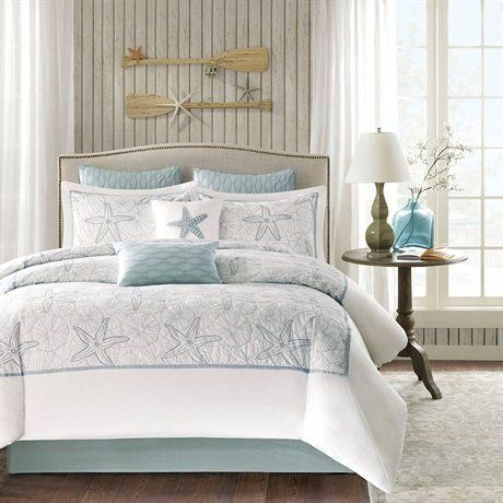 Get this Harbor House Crystal Beach 4-Piece White Comforter Set, which is perfect for a beach home because of its soft white and blue hues and relaxing overall vibe.