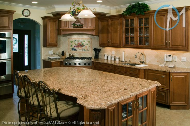 A large island is the centerpiece of this elegant design. The featured granite is Giallo Vicenza