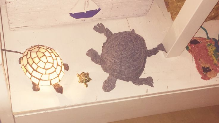 Crocheted turtle designed and made by Annikki Matthan 2015, alongside a Tiffany lamp and studded turtle.