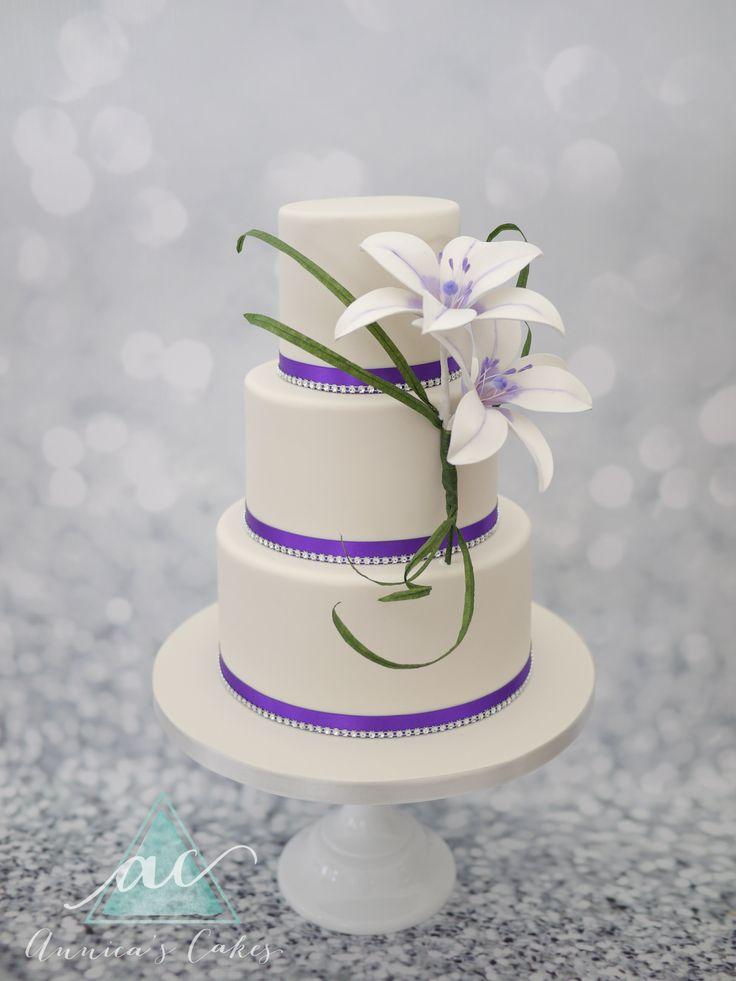 Wedding cake with sugar lilies and purple accents  Bruidstaart met lelies en paarse accenten