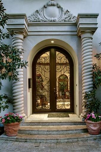 Elaborate columns bookending wood and glass doors. #portals #doors