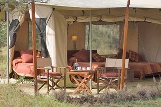 """Ndololo Safari Camp lies on the thick forested banks of the Tsavo river in Tsavo East National Park. The camp has 20 well spaced tents, each self contained with a verandah, furnished in a blend of ancient and modern with carved olive furniture and African artifacts. The local area is teaming with game, including the """"Big Five"""", and a wide variety of bird species. Activities include walking with guides, Bush BBQs, and evenings around the camp fire."""