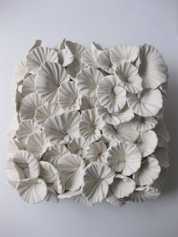 NEW to the line is the Maitake Mushroom Tile.  Each mushroom cap is delicately formed and arranged randomly to mirror natures sporadic scattering. Your piece will be similar, but all tiles are handmade and unique  There are two holes in the back of each tile for hanging flush against the wall.  Size: 7 x 3 depth Color: White Each tile is signed by the artist  * With many of the square tile species, color or shine may dull the details that polymer is renown for capturing. Veins and imprints…