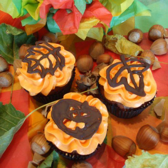 Herfstcupcakes met een oranje toef botercrème en zelfgemaakte chocoladedecoratie. Leuk om samen met de kinderen te maken in de herfstvakantie! Klik op de afbeelding voor het #recept. #cupcake #chocola #herfst