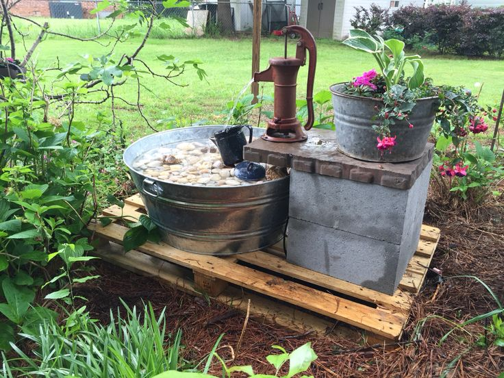 Antique water pump made outdoor fountain. Using a vintage tub as a planter.