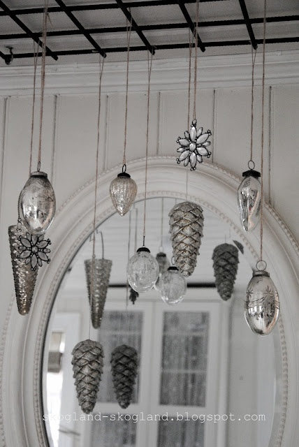 Hanging ornaments in front of a mirror to multiple a small collection ************* white & silver spray painted and glittered pinecones??hmmmmm..