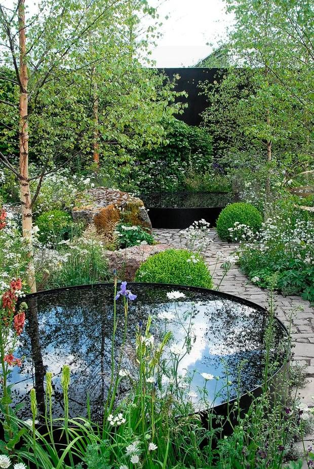 """Vand indgik, i mange af haverne, som et vigtigt designmæssigt element. Her i """"The Night Sky Garden"""" var det i form af et par store, runde spejlbassiner, der reflekterede himmelhvælvet. De mange hvide blomster symboliserede nattehimlens lysende stjerner, mens de store sten gav mindelser om nedfaldne meteorer. Alt forenet i et raffineret design."""