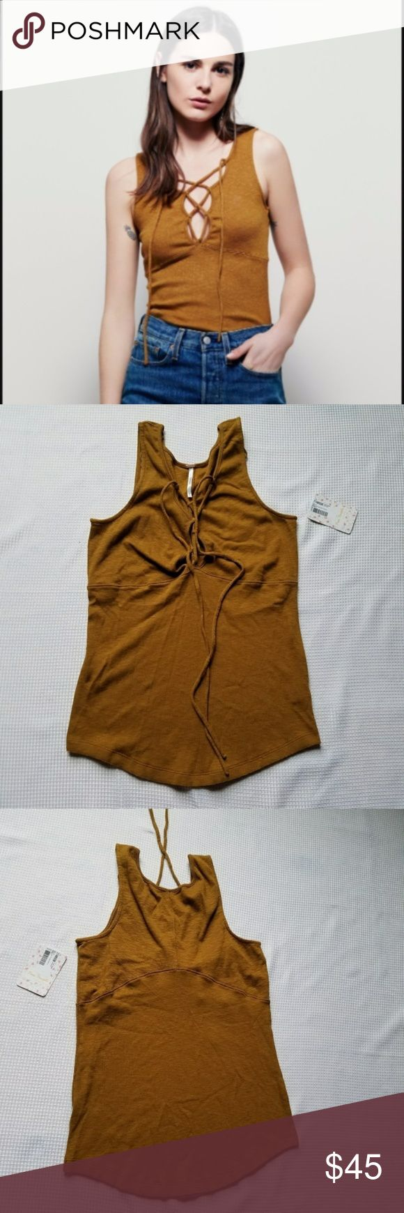 """Free People Emmy Lou Bronze Top M Women's tank. Made with a double layered rib stretch fabric. Deep V neck with lace up detail. Seaming along the bust. Rounded hem. Snug fit. Sleevelesss. Armpit-to-armpit: 15"""". Shoulder to hem length: 23"""". 58% cotton, 38% modal, 4% spandex . Machine wash cold, dry flat. boho bohemian criss cross tie gypsy hippy hippie casual desert western southwestern Free People Tops Tank Tops"""