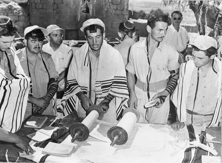 "Orthodox Jews of the Israeli Army read the Torah of Holy Scrolls, during commemorations of the Jewish fast day Tisha Bav, in Tel Aviv, Israel, Aug. 19, 1948. The Jewish signs of mourning, ""Tvilum"" around the arms and on the forehead, are worn by the men and those who are also married wear shawls. (AP Photo) Ref #: PA.5755037 Date: 19/08/1948"