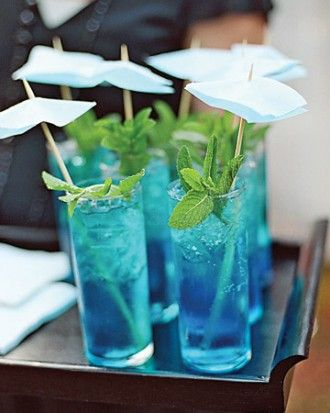 If blue is your color scheme, blue mojitos garnished with mint sprigs are the perfect wedding cocktail. These are topped off with Blue paper umbrellas that were inspired by the brides dress.